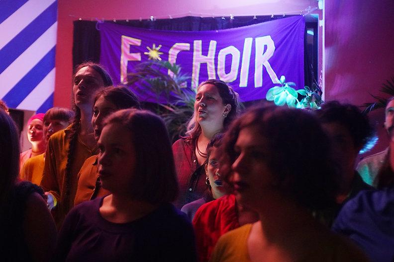 Members of the choir sing under pink lig