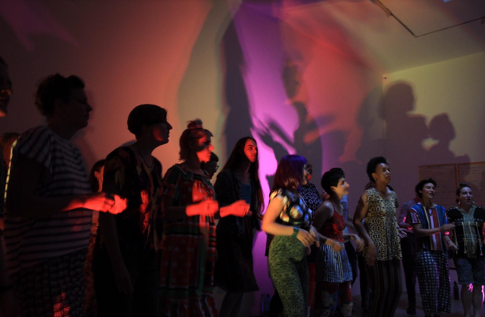 13 performers stand infront of a wall, lit by pink, purple and blue lights. Their shadows project on the wall behind them. They wear patterned clothing and their hands are blurry with movement.