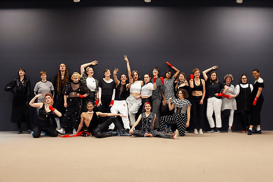 F* Choir members pose in a group, wearing black and white with red gloves, at Borealis Festival