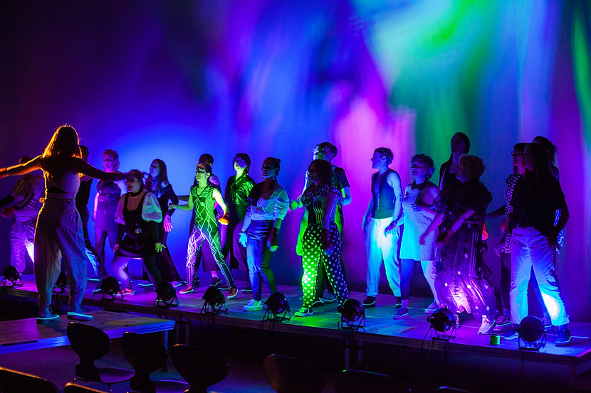 F* Choir concert, Not Dancing, Fighting, at Borealis Festival for Experimental music in Bergen, Norway Photo credit: Johanne Karlsrud/Borealis  Image description: Performers on a stage are lit by blue, purple and green light. They face Jenny who is conducting with arms open.