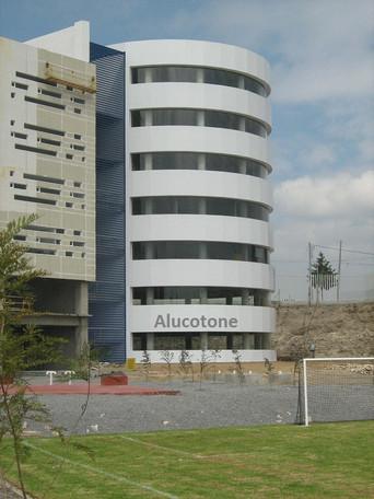 Fachada con Panel Aluminio Compuesto Alucotone sobre bastidores PTR sujetos a losa de Obra Civil, luego de Panel Alucotone se reciben ventanas cristal curvo.