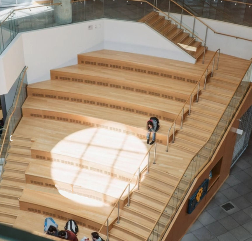 Hangout Stairs at a University that are inaccessible to people who use a wheelchair or mobility aid, no tactile or colour contrasting features for people who are blind or vision impaired, loud space for people who are hard of hearing