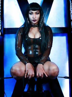 Sitting in from of a piece of bdsm and s&m furniture femdom mistress scarlet vexus sits holding crop