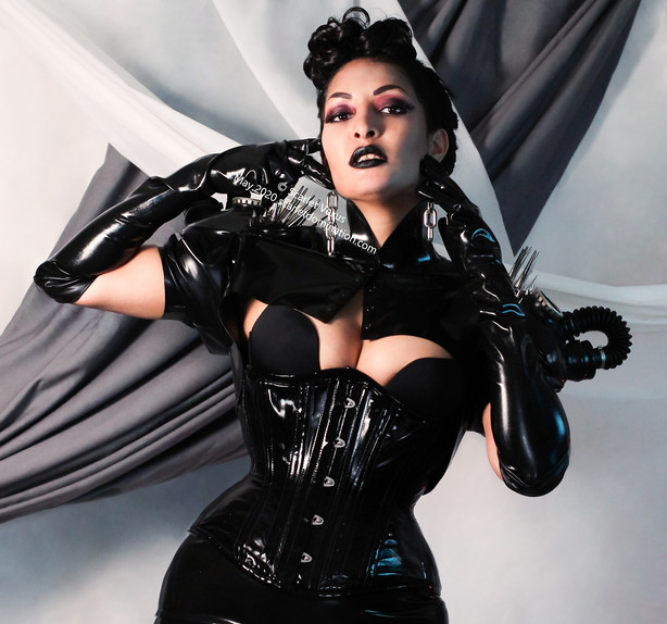 wearing a latex outfit mistress scarlet vexus poses in a corset