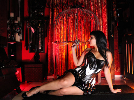 mistress scarlet vexus sits in front of a femdom piece of furniture