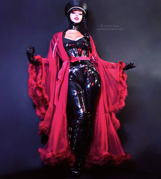 Austin Dominatrix Scarlet Vexus wearing a latex catsuit and lace shawl