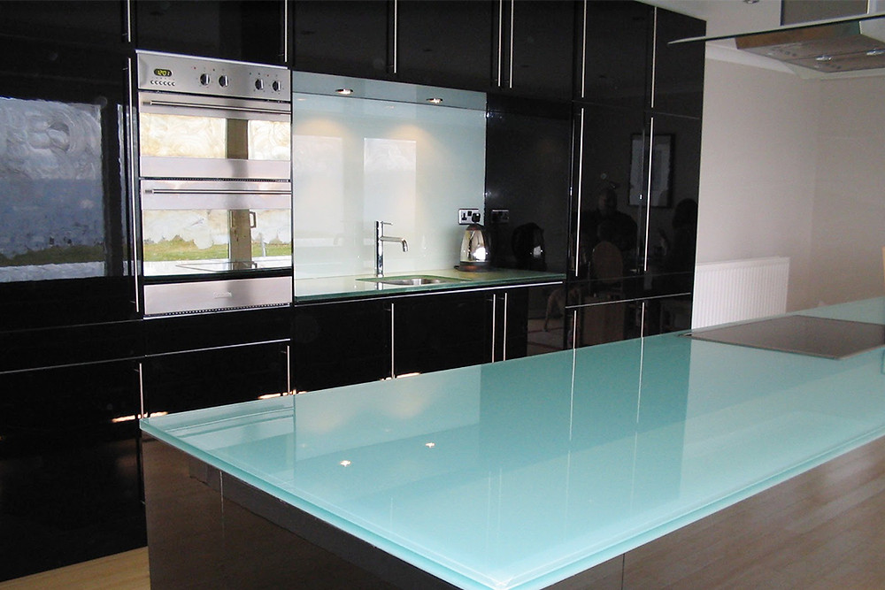 monochrome kitchen with white glass splashbacks and black units