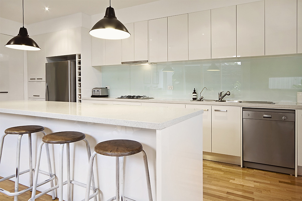 Modern white kitchen with white glass splashbacks