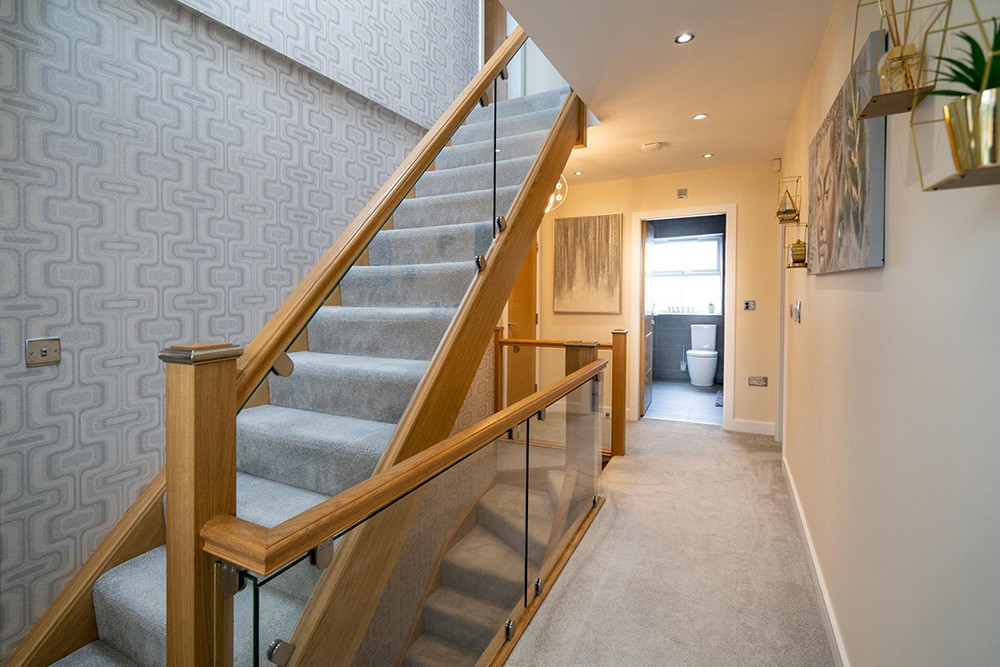 Glass staircase balustrades with oak handrail and posts in a modern home