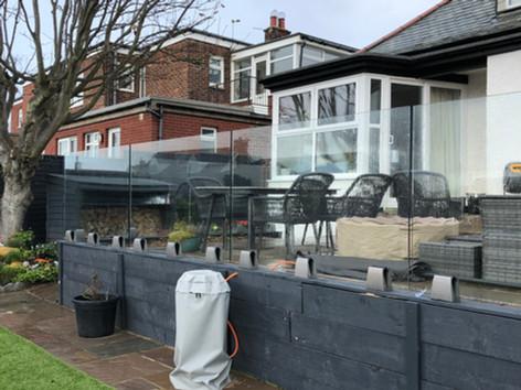 Glass balustrade for raised patio