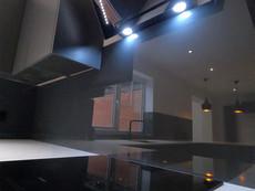 Glass splashbacks in black painted toughened glass for monochrome kitchen
