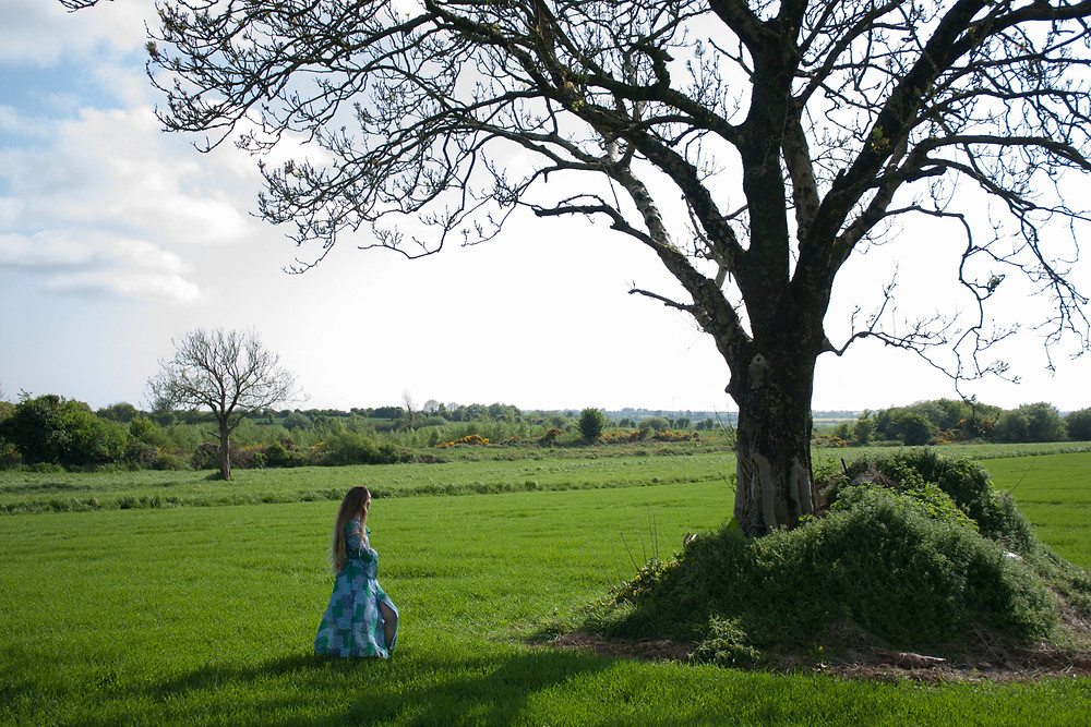 Model standing in an open field by a tree. wearing a blue and green mid length button down dress. Irish made Cobbler's Lane fashion design