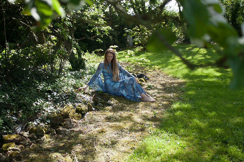 Model is sitting in a wooded area wearing a mid length blue dress with an intricate print. the dress has a large bell sleeve.