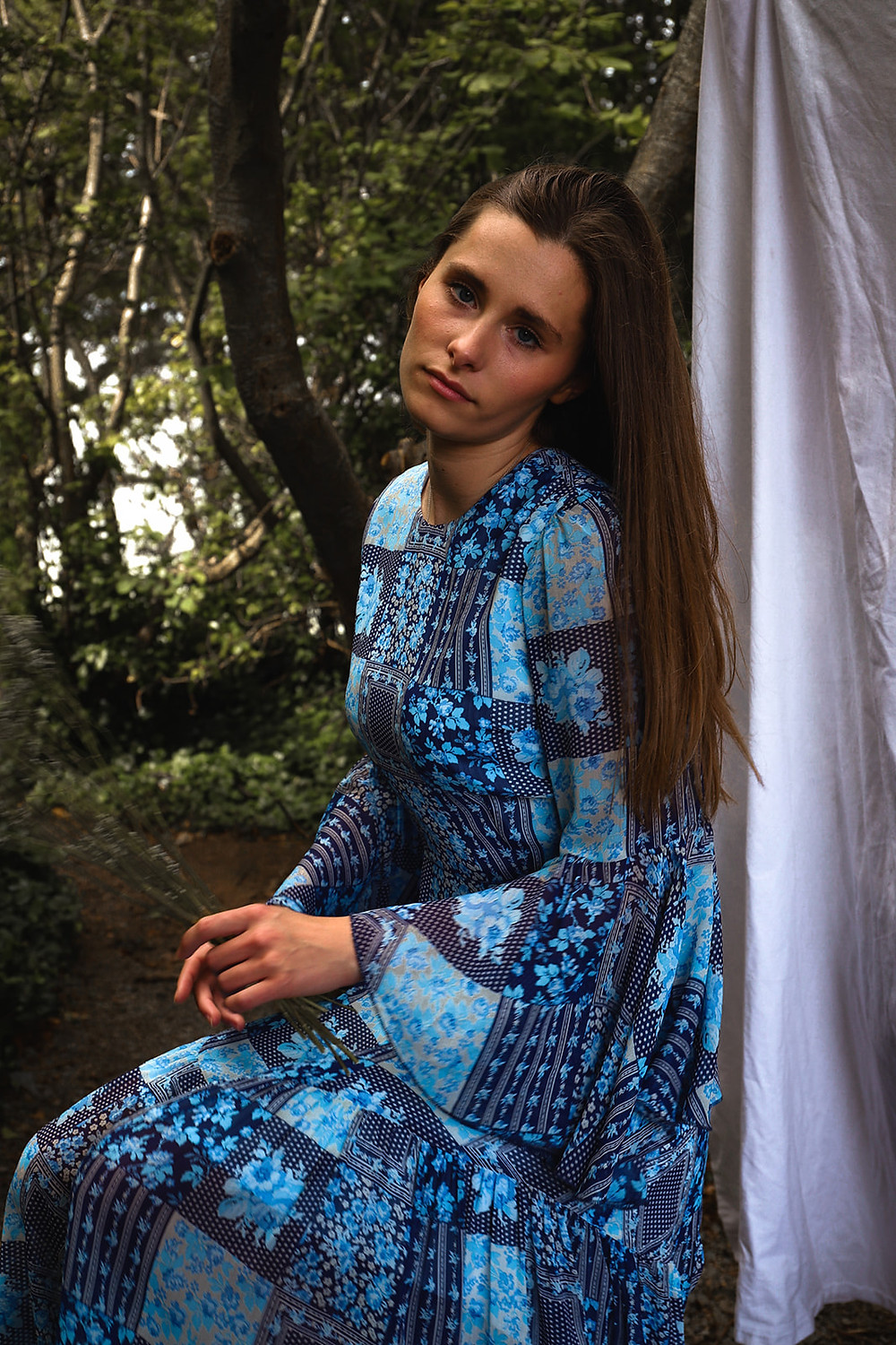 Model wears a blue floral print dress with a long bell sleeve and an A-line miid length skirt.