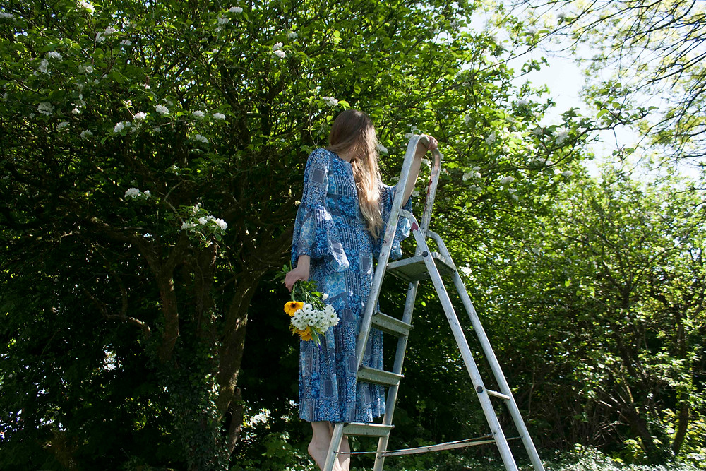 Blue tile print dress with a bell sleeve and gathered skirt. Standing on a ladder under a flowering apple tree holding a bunch of flowers. Cobbler's Lane is an irish fashion brand. the dress is made in ireland