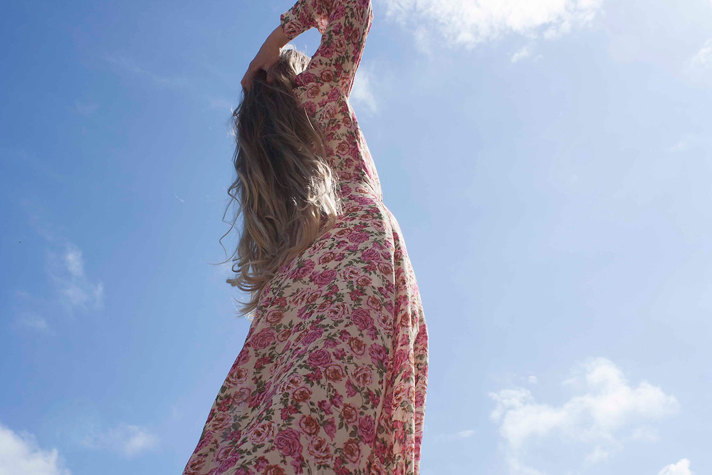 pink rose print maxi dress against a blue sky. the model has long blonde hair. the rose print dress is made by Cobbler's Lane has long sleeves and an open back
