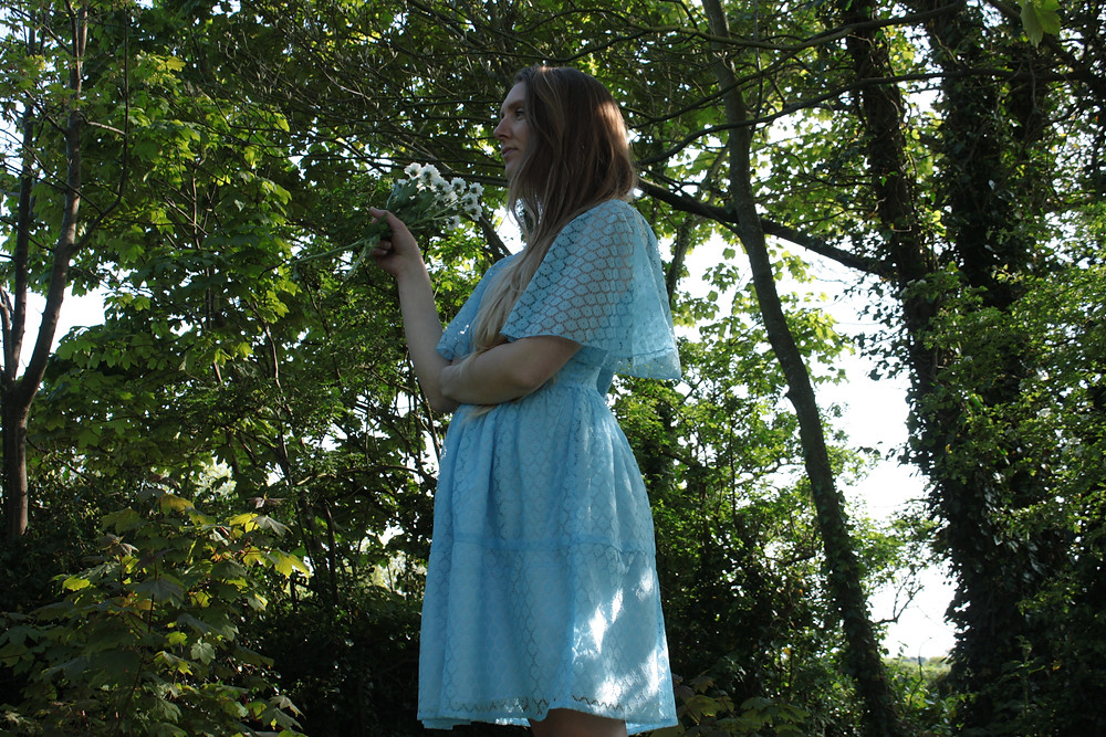 Irish made Cobbler's Lane designed. Girl stands in a wooded garden surrounded by trees holding a bouquet of flowers. she is wearing a light blue delicate lace mini dress.