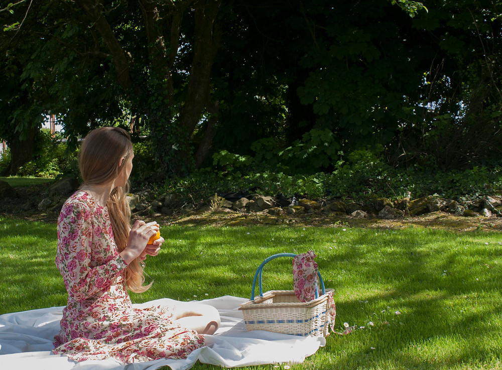 Girl sitting in a green garden surrounded by trees. she is peeling an orange and wearing a pink rose print dress dress with long sleeves.