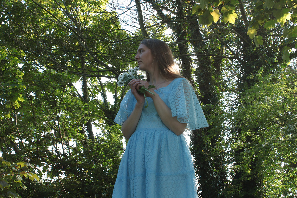 Girl wearing a pale blue lace dress. the Cobbler's Lane design has a flared sleeve and a full skirt gathered at the waist. The female model in standing in a wooded area holding a bunch of daisies