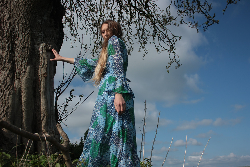model stand with hair down by a large old tree. blue sky. wearing a blue and green tile print dress with ruffle sleeve, long sleeve, button up midi dress.