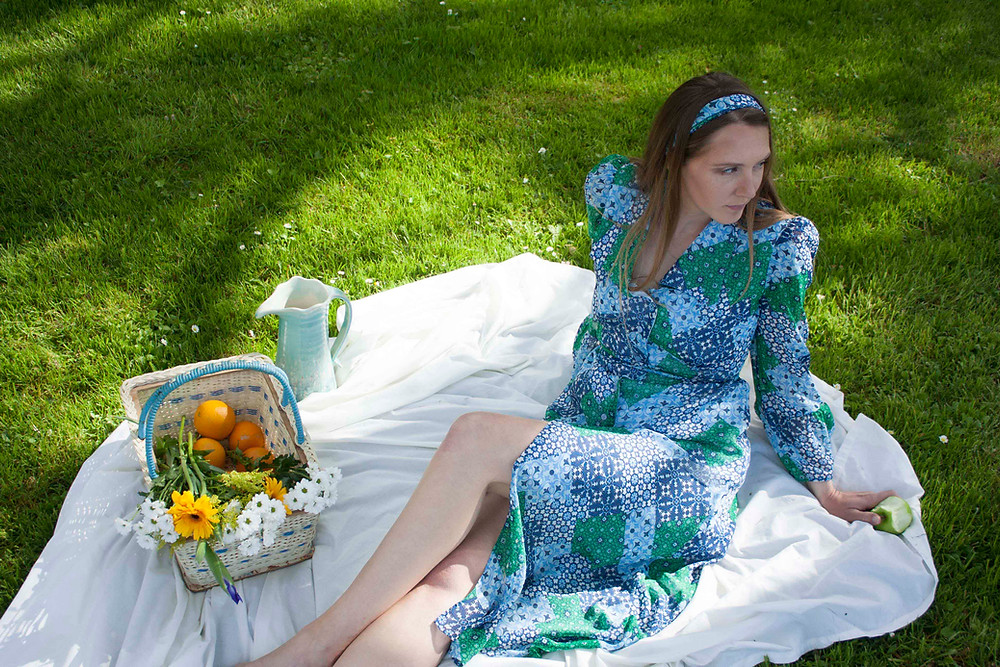 model is lying on a picnic blanket on the grass with a basket filled with oranges and flowers. she is wearing a blue and green print dress with a matching head scarf. the Cobbler's lane design dress is Irishmade and has a statement collar, button down front, long sleeves with a flared detail. and a belted waist.