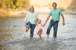 family kicking water in river