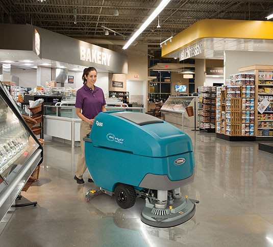 Walk behind automatic floor scrubber in use