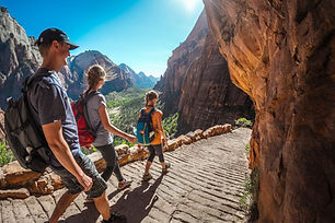 Group of hikers friends walking down the stairs and enjoying view of Zion National Park, U