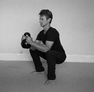 Trainer demonstrating a Goblet Squat