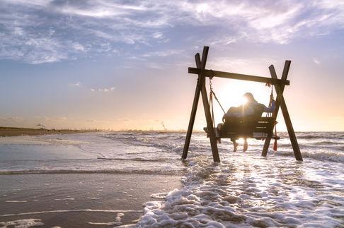 Loveshoot met koppel in schommel tijdens zonsondergang in Hoek van Holland aan het strand