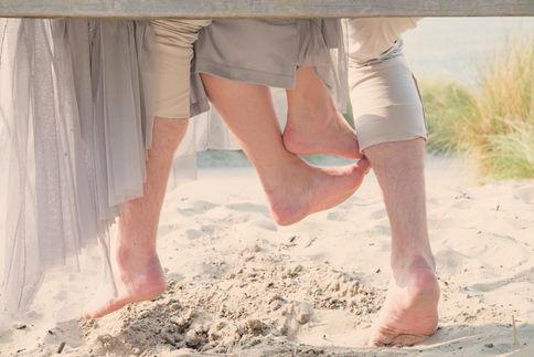 Koppel is stiekem aan het voetjevrijen tijdens een loveshoot in de duinen van Rockanje