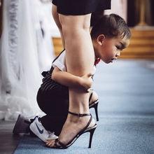 zoontje verveelt zich en hangt tussen de benen van een bruidsmeisje gedurende de ceremonie