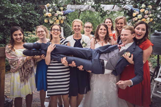 Groepsfoto waarbij de bruidegom wordt gedragen door de meiden @Rotterdam