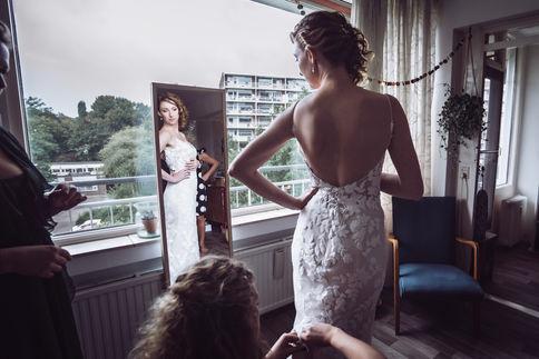 Bruid bekijk haar bruidsjurk voor de spiegel