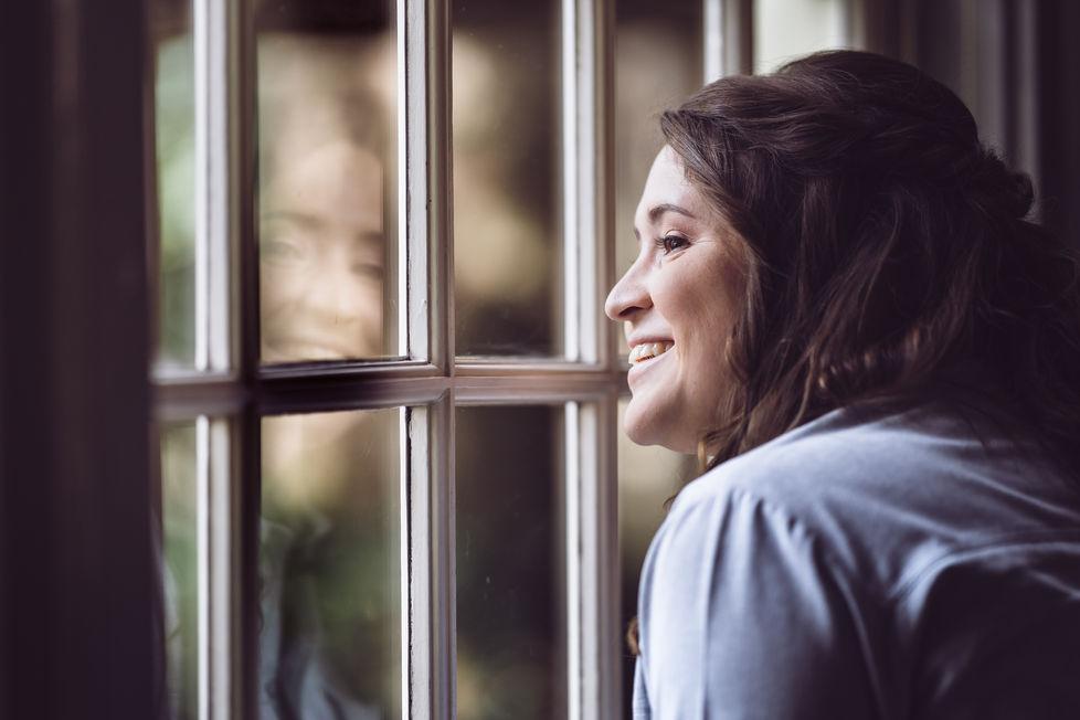 Bruid kijkt uit raam om te kijken of haar verloofde er al aankomt @Rotterdam