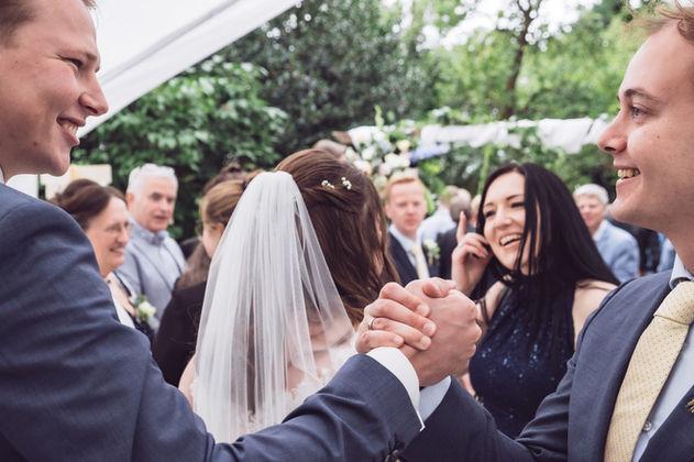 Bruidegom wordt gefeliciteerd door zijn beste vriend na verbintenis