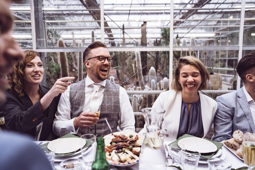 Bruidspaar en gasten vermaken zich tijdens diner