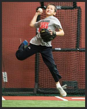 Kid jumping and throwing a baseball