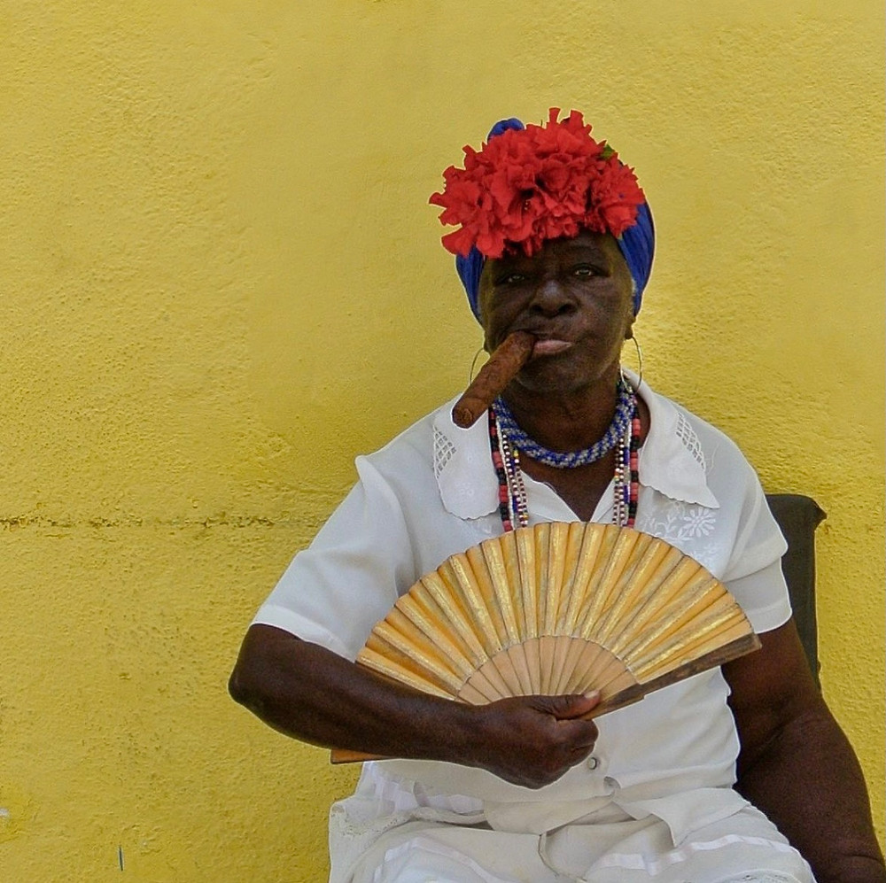 Cuban lady with pungent blue hair wrap and a bright red flower attached to it, smokes a cigar while sittingon a brown wooden chair against a bright yellow backdrop, fanning herself with a mellow yellow hand fan