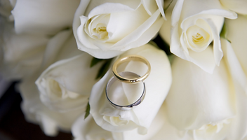 A photographt of white roses with a pair of wedding bands laid over the top