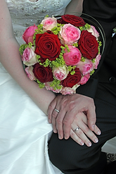 Bride and groom holding hands with a wedding bouquet