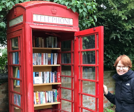 photo red phone booth of books