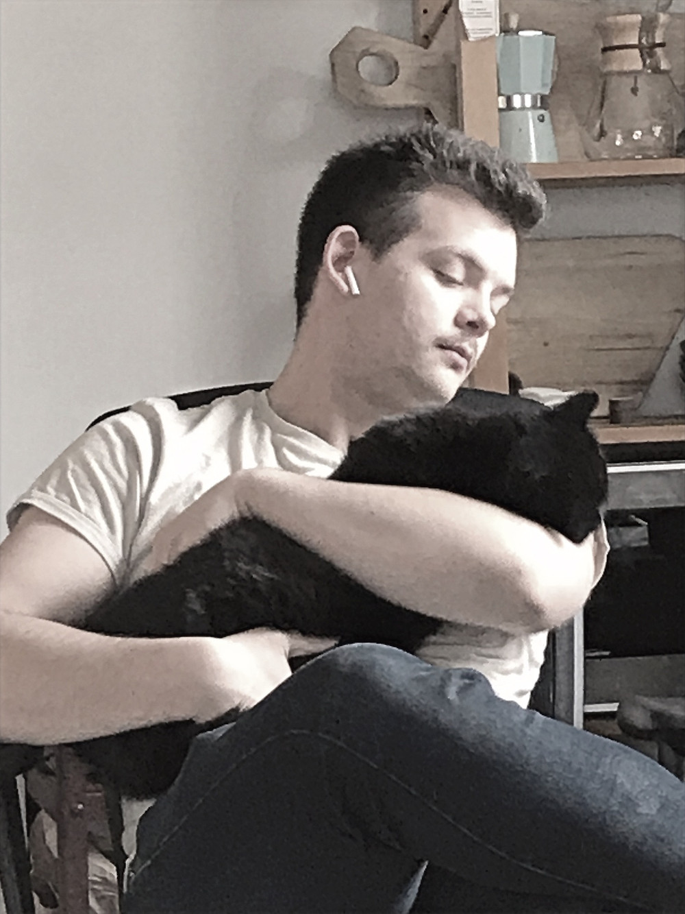 A man lovingly holds his large black cat.