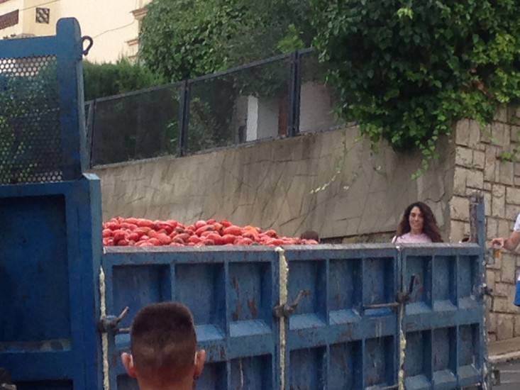 La Tomatina starts with people crowding the narrow streets, kind locals throwing buckets of water or