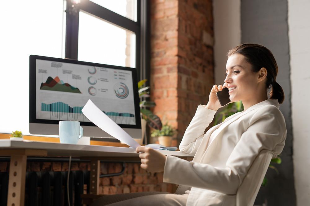 Dans un cadre de bureau moderne, une femme au téléphone est en train de lire un rapport sur une feuille, devant son ordinateur allumé.