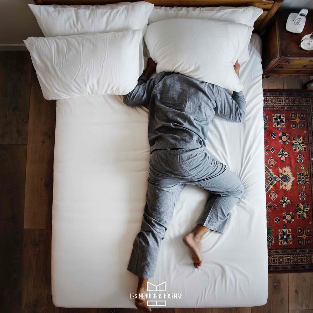 Un français allongé, probablement endormi, tient un coussin sur sa tête pour se protéger du bruit.