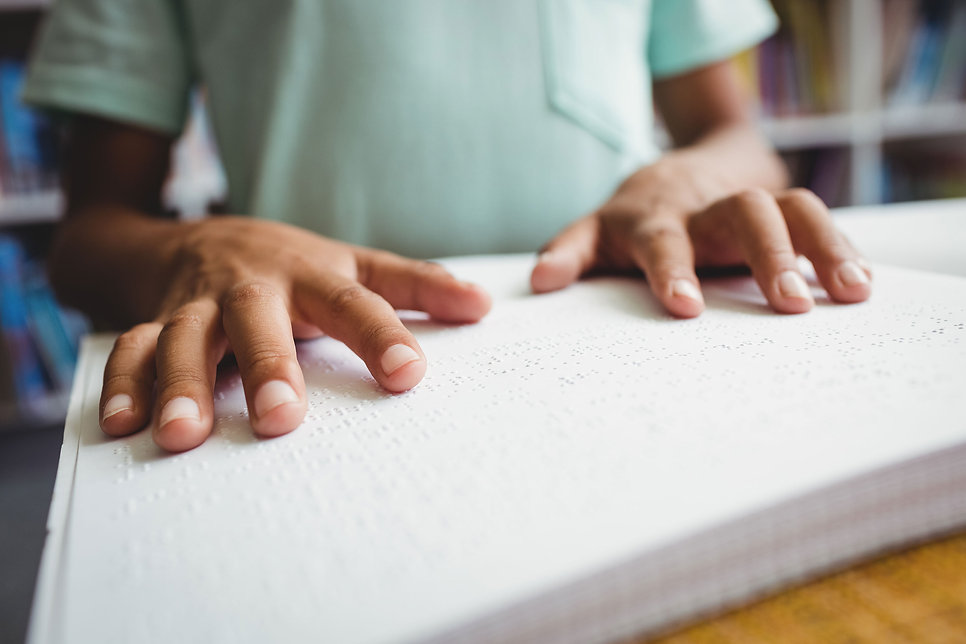 A little boy is using braille to read a story