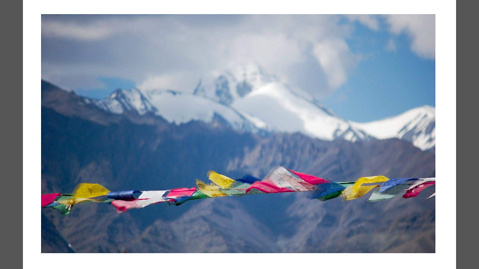 Prayer flags hang in front of Himalayas, Ladakh.