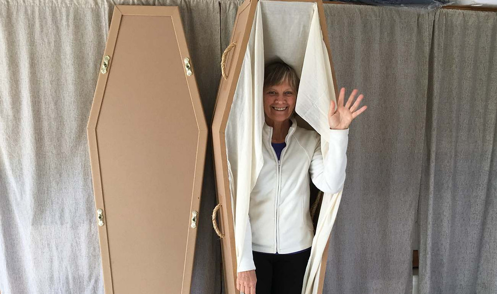 Ingrid Langenbruch waving out of her cardboard coffin, prepared to pass over