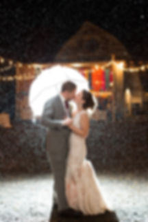 Bride and Groom kissing in rain
